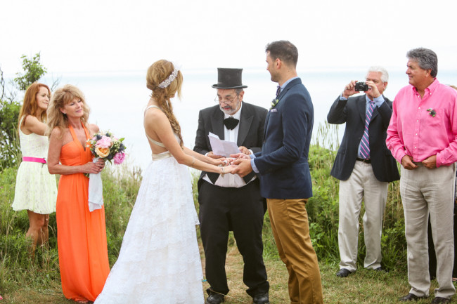 bride and groom hold hands and overlook sea at Martha's Vineyard wedding ceremony