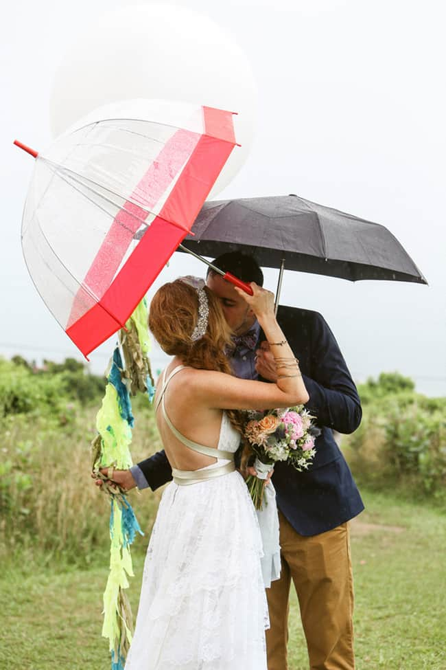bride and groom kiss under umbrellas in the rain at Martha's Vineyard