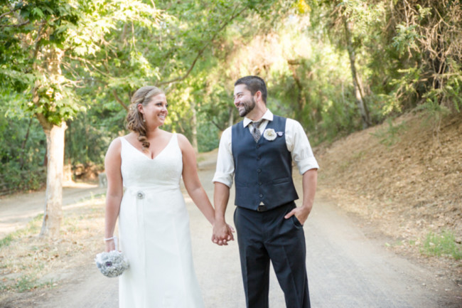 bride and groom hold hands on dirt road