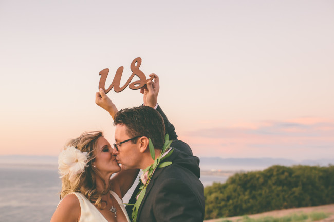 couple kissing while holding letters that spell 'us'