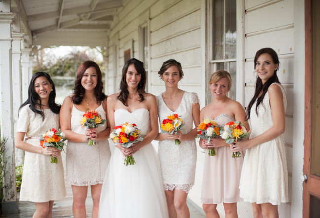 bride and bridesmaids in white dresses holding red, yellow, and white bouquets
