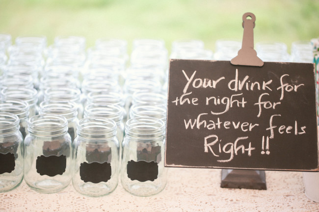 "mason jars lined up with sign instructing guests, ""Your drink for the night for whatever feels right!"""