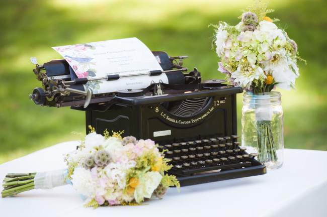 old typewriter next to flower bouquets