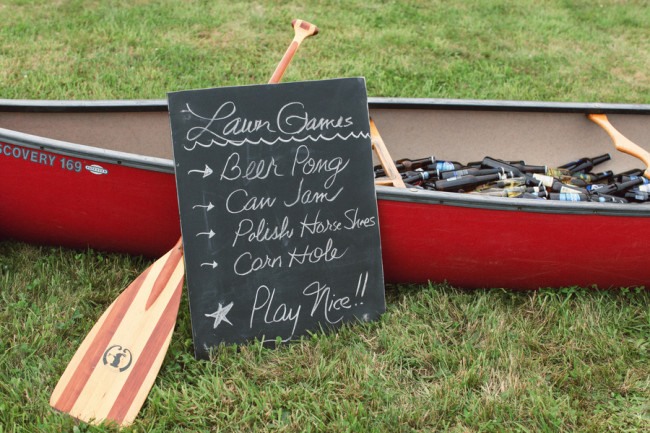 red canoe overflowing with beer bottles; chalkboard lawn game sign leaning against
