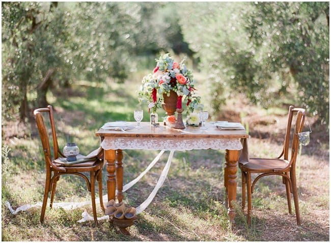 styled ornate table and two chairs in middle of olive grove