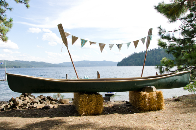 Caoe on hay stack with oars and bunting infront of lake