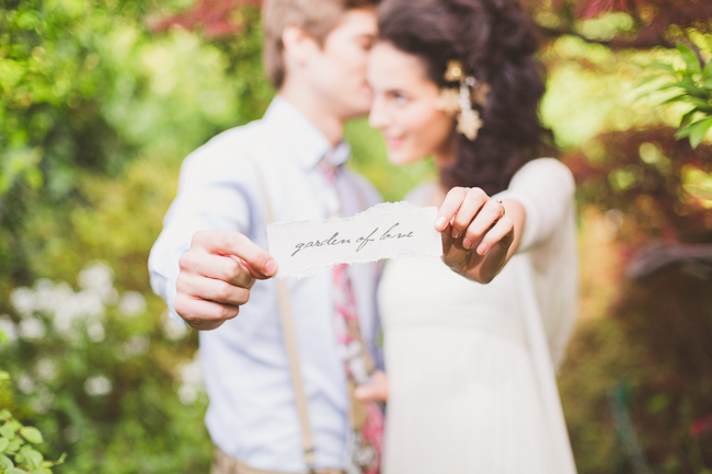 Bride and Groom holding a garden of love sign