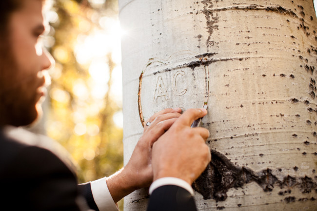 Groom carving initials into tree