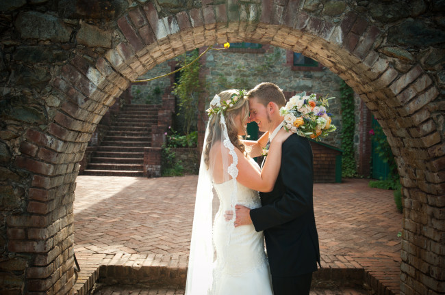 Bride and groom, brick archway, wedding boquet