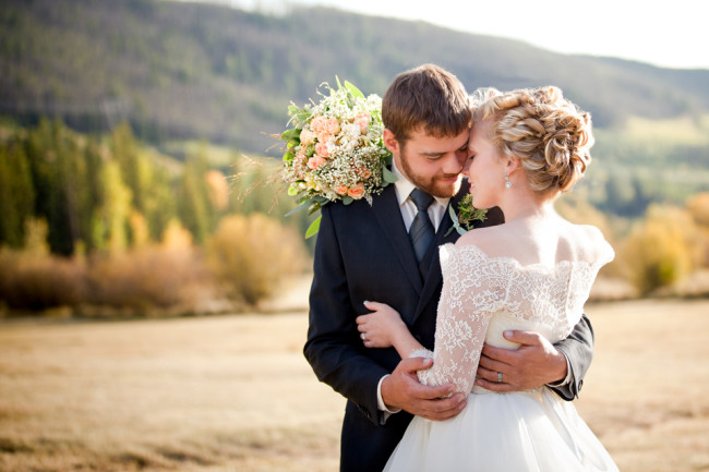 Bride and Groom outside posing with wedding bouquet