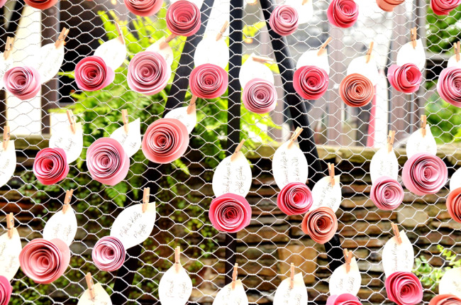 Seating chart made out of paper roses on chicken wire,