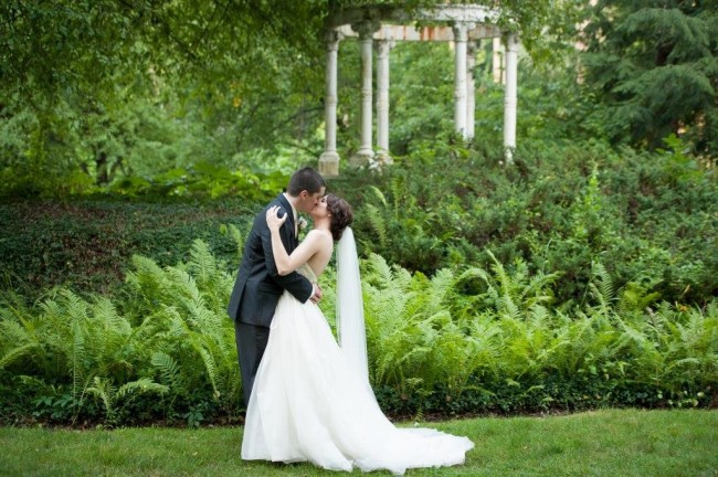 Bride and groom kissing on grass
