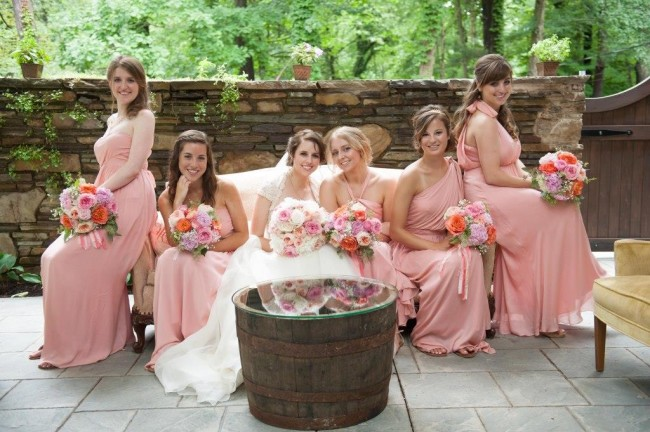 Bride with bridesmaid sitting on a couch infront of a barrel
