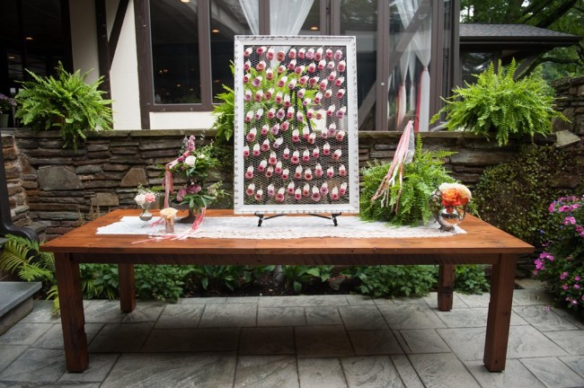 Searting chart with paper roses hanging from chicken wire on a table