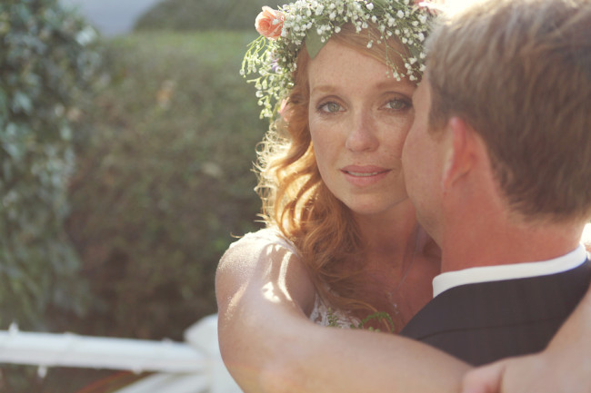 bride with floral crown looks stunning in the sunny backdrop lighting