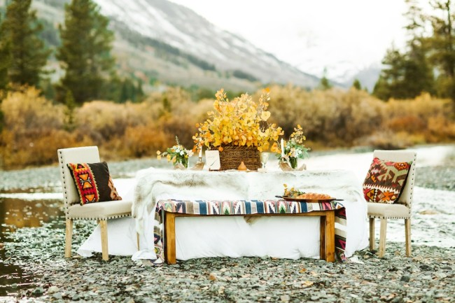 rustic boho Colorado table beside Slate River with blankets, fur, & Aztec pattern pillow