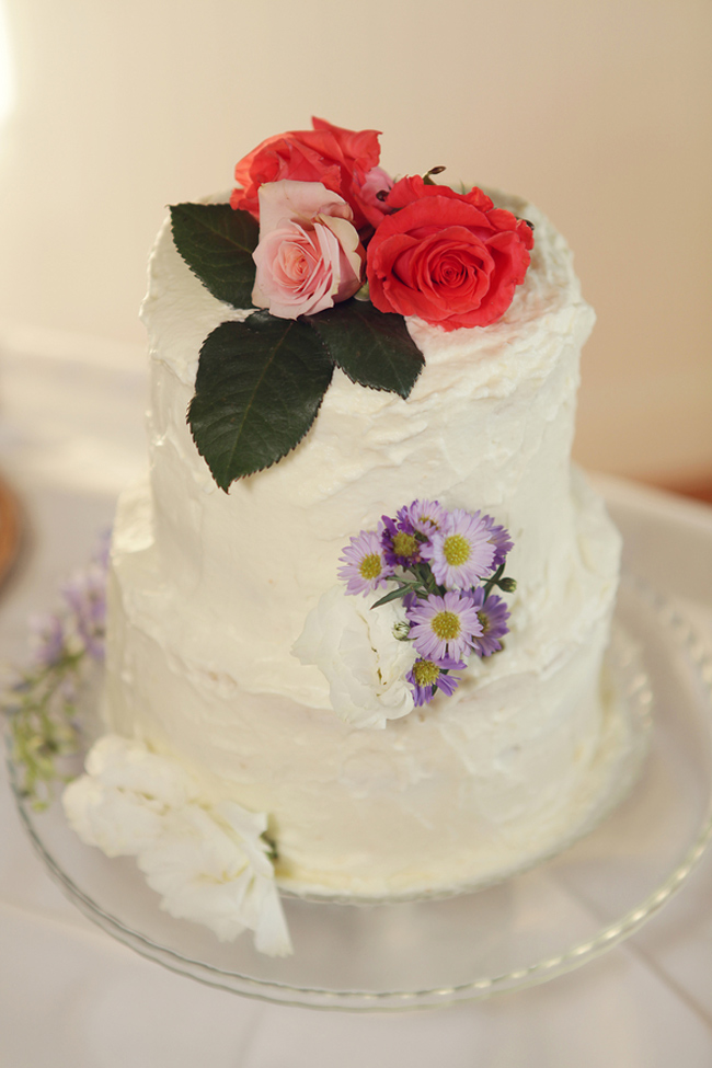 wedding cake with bright pink roses and rose leaves as cake topper