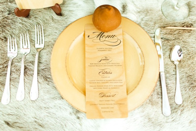 place setting with menu card, pear, and cutlery on fur tablecloth
