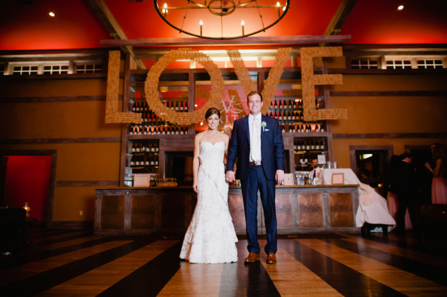 bride and groom stand in front of giant LOVE signhanging over bar