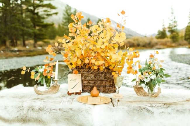 rustic boho tablescape with orange aspen fallen leaves, pear, and fur blanket