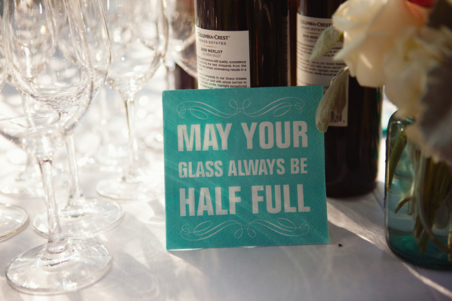 "wedding drink table with sign that reads ""May your glass always be half full"""