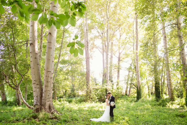 bride and groom embrace in the forest