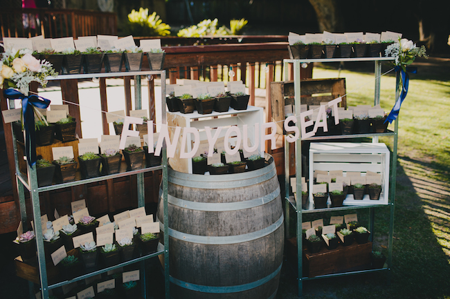 "wine barrel with banner ""Find your seat"". Succulent plants for table seating on top and beside"