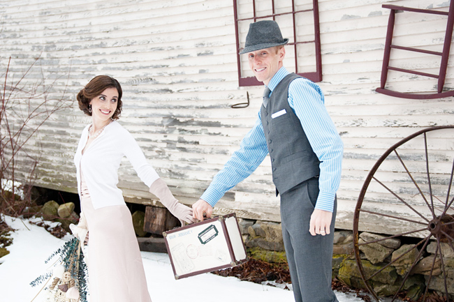 husband in fedora holds vintage case with wife