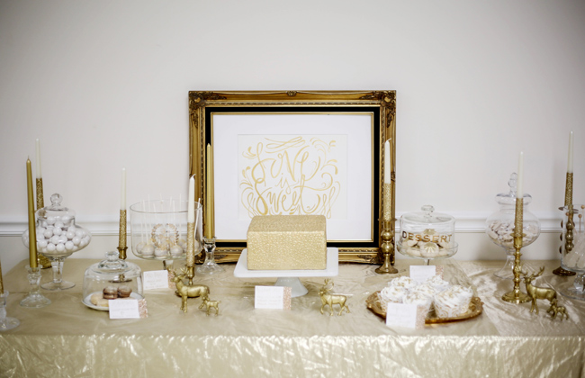gold picture frame with gold decor on dessert table