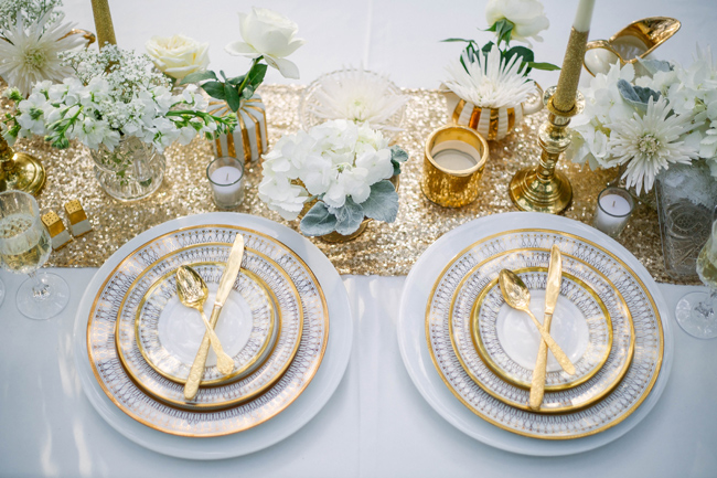 gold cutlery and gold rimmed china plates on table setting