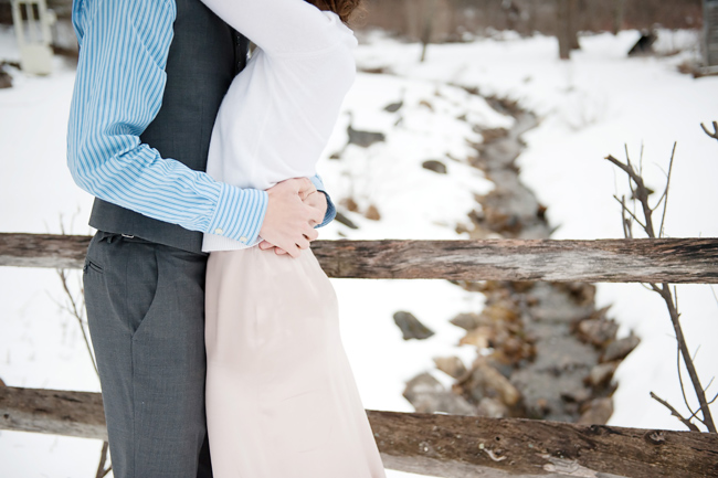 couple embrace on wood bridge over snowy brook