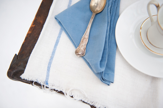 silver spoon on blue napkin with tea cup