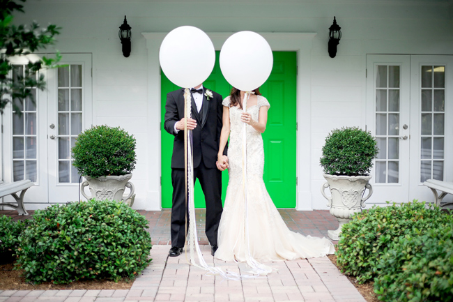 bride and groom hold geronimo balloons in front of faces