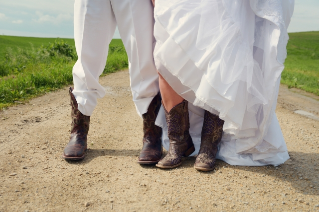 Bride and groom in their cowboy boots outside