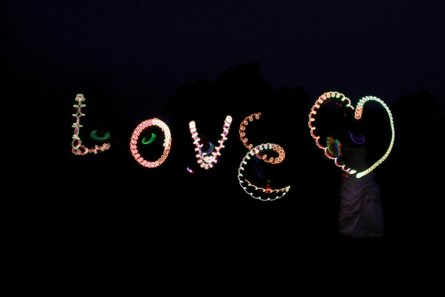 "night time sign with lights that says ""love"""