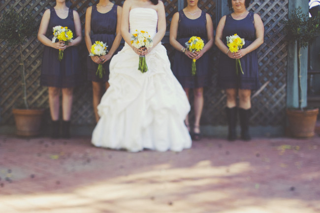 bridesmaids with navy blue dresses holding yellow flowers