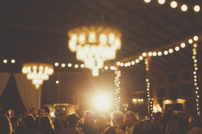 Party under chandelier lights hanging from Dana Powers House Barn wedding reception