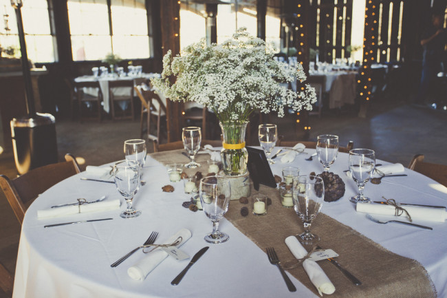 baby's breath flowers in vase on table centerpiece with burlap table runner