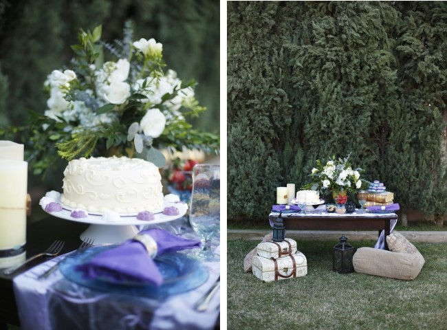 Dessert table with cake and purple macaroons set against large hedge. Vintage suitcases and black lanterns at base