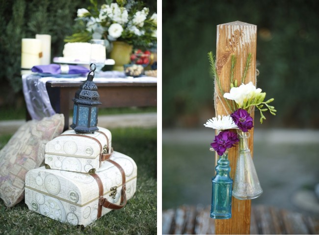 White vintage inpired luggage with black lantern on top, flowers hang from wood post in jars