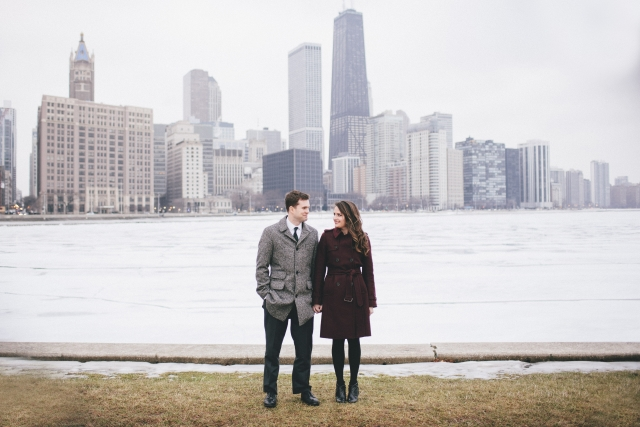 Chicago Cityscape engagement shoot couple stand on edge of water with Chicago in background