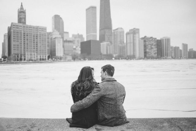 Black and white photo of Chicago Cityscape engagement shoot couple sitting on ledge with Chicago in background