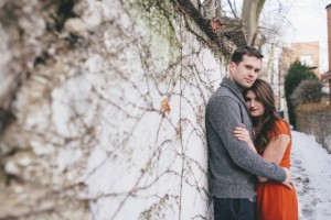Engagement shoot couple stand against white wall in late Fall weather