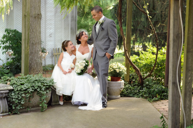 Groom standing, bride and flower girl sittiing on stone bench