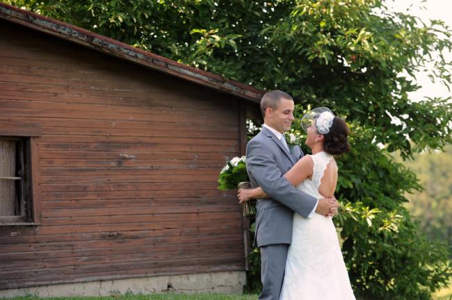 Bride and groom hug next to old barn