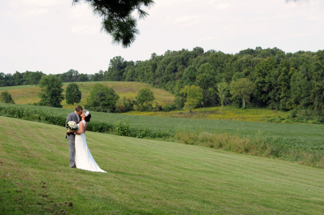 Bride and Groom kissing on the middle of rolling hillside