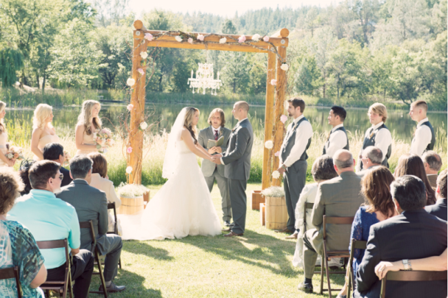Wood beam alter with roses and vines, chandelier hanging from middle as bride and groom take their vows