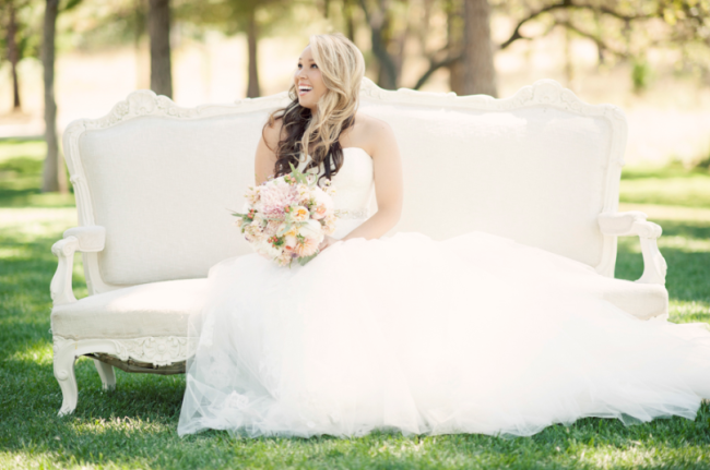 bride sitting on white vintage couch at Leaning Tree Lodge wedding