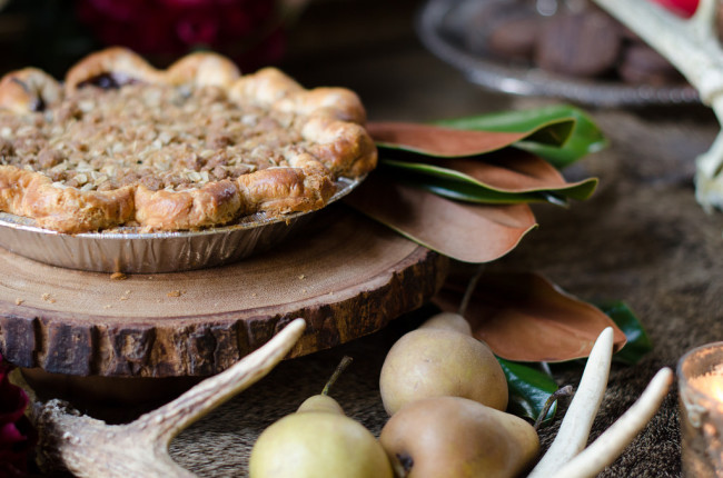 fdelicious looking pie on wood round with pear and antler decor