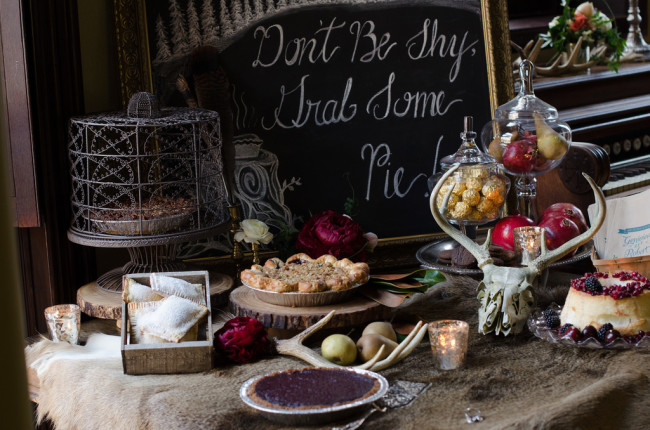 dessert table with pies, apples, antlers, and chalkboard sign